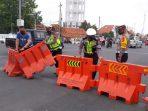Sejumlah petugas tengah memasang alat penyekat di salah satu ruas jalan.